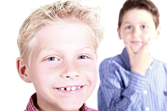 Blond-włosy chłopiec uśmiecha się