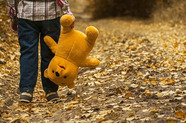 Dziecko z misiem w ręce idzie ścieżką
