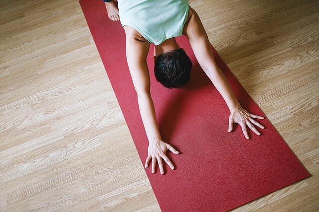 Dziewczyna ćwiczy jogę na czerwonej macie