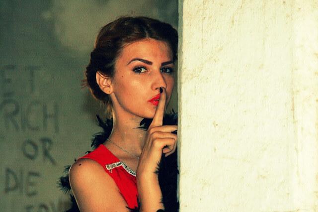 Tajemnicza kobieta gestem pokazuje, że zapada cisza