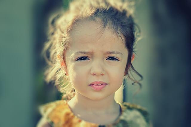 Dziewczynka marszczy brwi, gdyż razi ją słońce