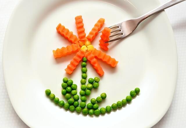 Groszek i marchewka ułożone w formie kwiatka na talerzu