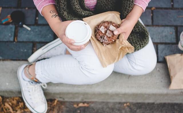 Kobieta siedząca na schodach z jedzeniem