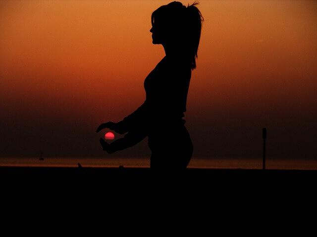 Kobieta trzyma w ręce miniaturę słońca