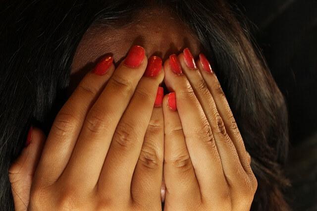 Wypielęgnowane dłonie kobiety zasłaniają twarz