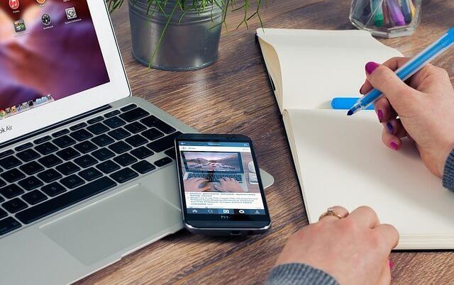 Pracujący człowiek z notatnikiem, komórką i laptopem