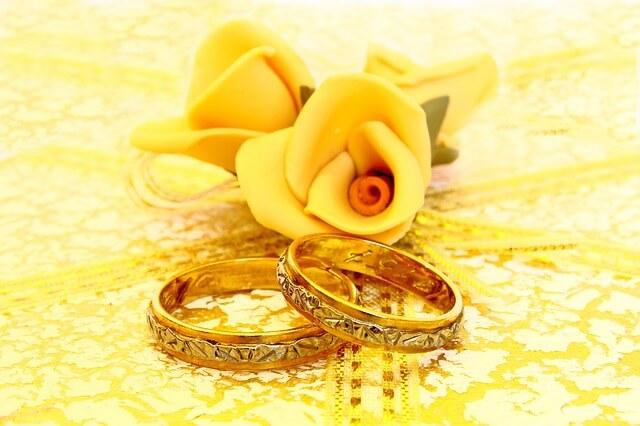 Żółta róża z modeliny leży na starodawnych obrączkach