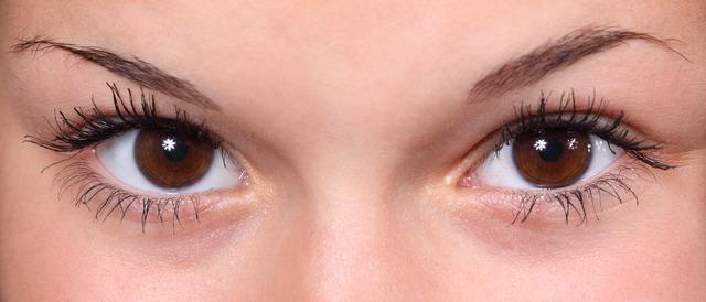 Kobieta spogląda pięknymi brązowymi oczami