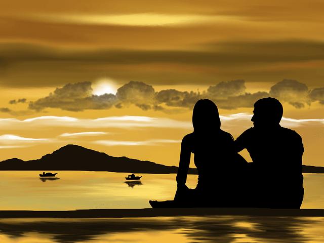 Para siedzi nad brzegiem jeziora i podziwia zachód słońca
