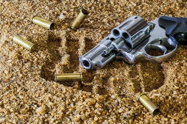 Rewolwer i naboje na złotym piasku