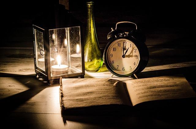 Książka, zegar i świeczka tworzą nastrój tajemnicy