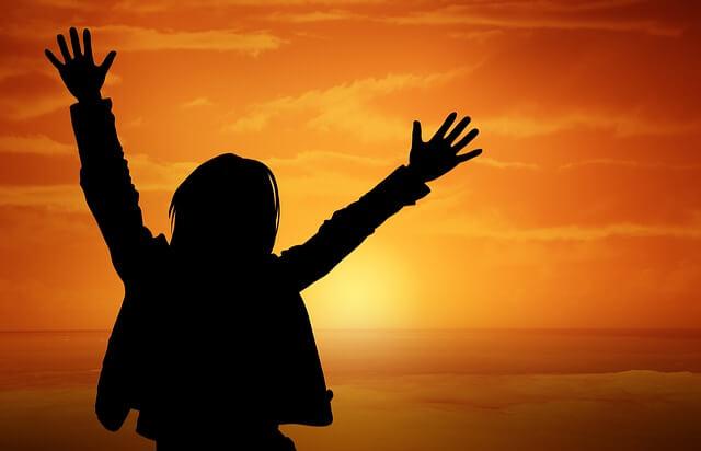 Szczęśliwa dziewczyn na tle zachodu słońca