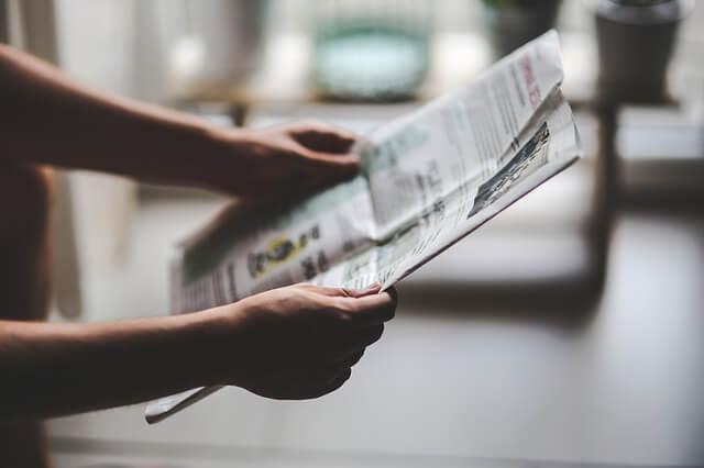 Mężczyzna czytający ogłoszenie w gazecie