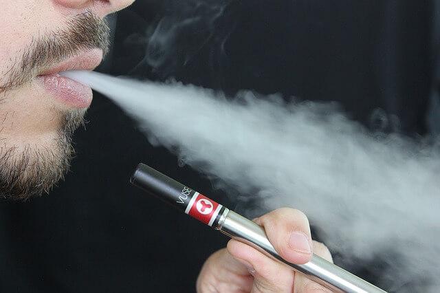 Mężczyzna palący e-papierosa
