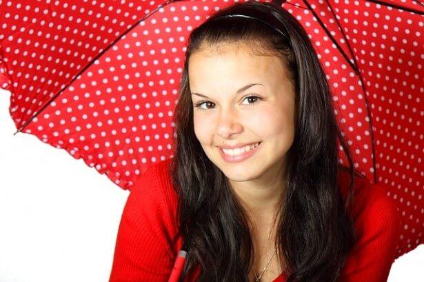uśmiechnięta dziewczyna pod parasolem