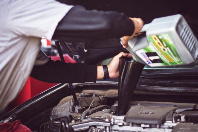 Mężczyzna dolewa oleju do silnika
