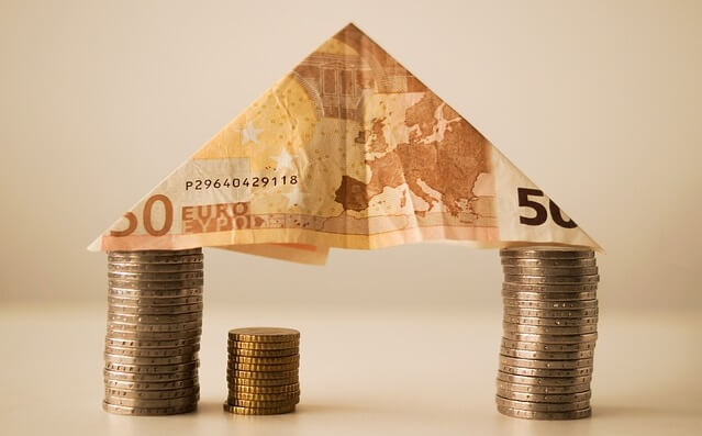 Banknot i monety ułożone w dom