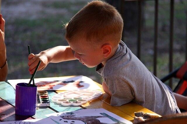 Chłopczyk maluje farbami na dworze