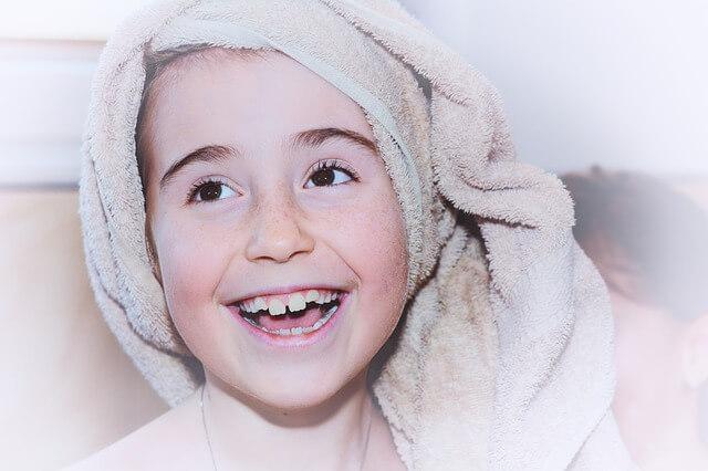 Uśmiechnięte dziecko z frotowym ręcznikiem na głowie