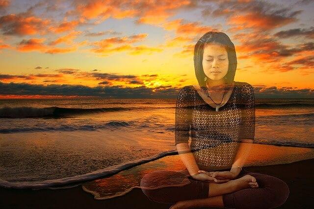 Dziewczyna ćwiczy jogę na tle zachodzącego słońca