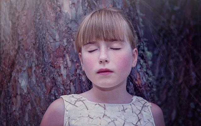 Nieśmiała dziewczyna opiera sie o stare drzewo