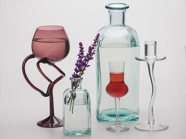 Butelki ustawione obok siebie, w jednej z nich kwiat lawendy