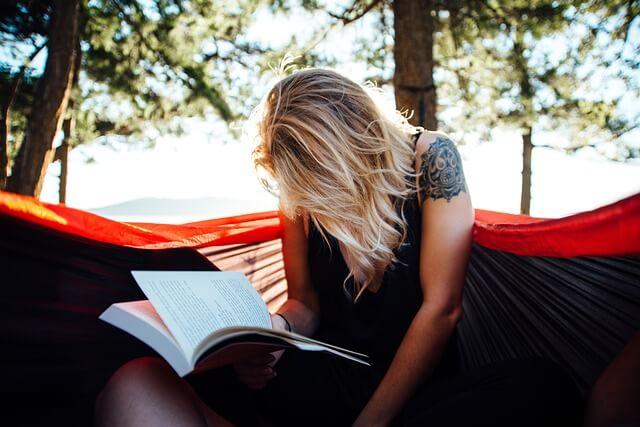 Blondwłosa kobieta siedzi pochylona nad książką