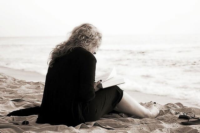 Kobieta w czarnej sukience siedzi nad brzegiem morza i czyta