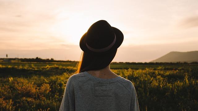 Kobieta w kapeluszu stojąca tyłem na polu
