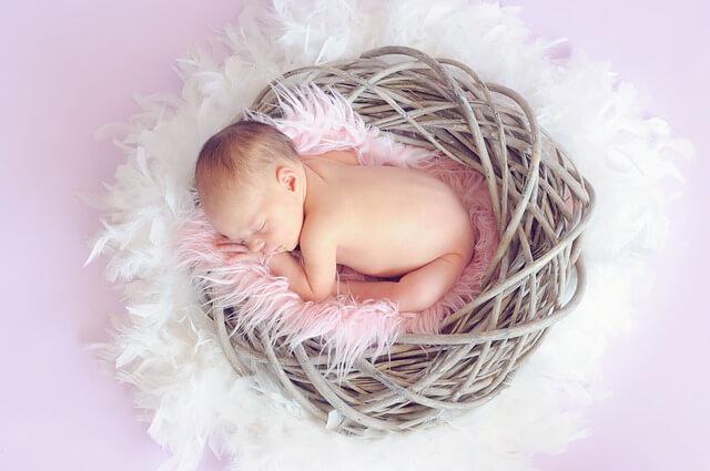 Małe dziecko śpi w gniazdku wyłożonym różowym puchem