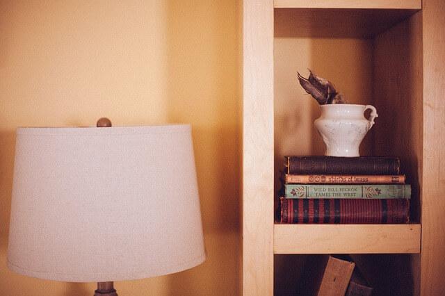 Prosta szafka, na której leżą książki i stoi lampa