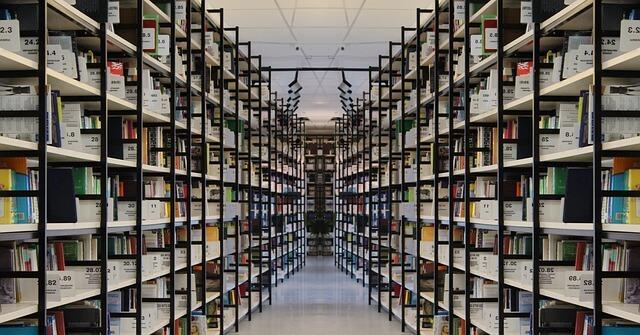 Równolegle ułożone półki z książkami w bibliotece
