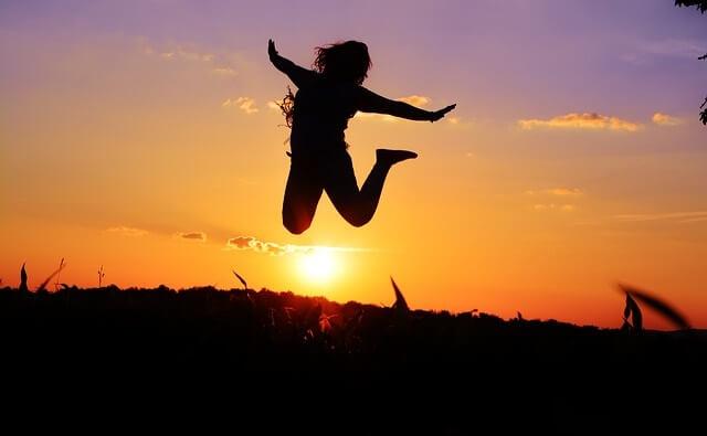 Sylwetka skaczącej radosnej kobiety