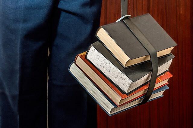 Grube książki przypięte do pleców czytelnika