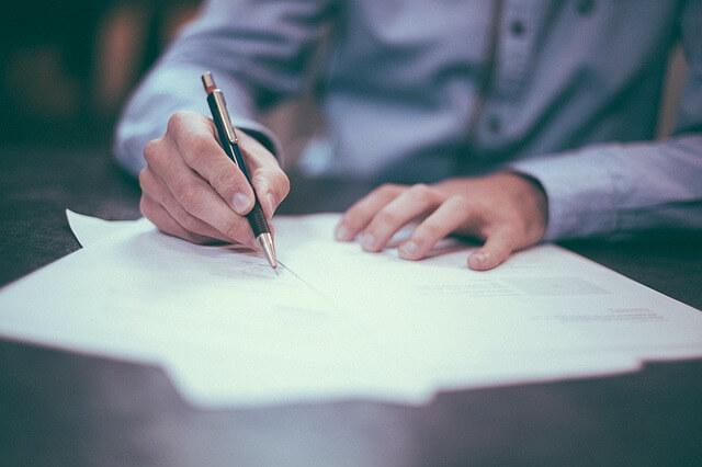 Mężczyzna podpisujący piórem umowę