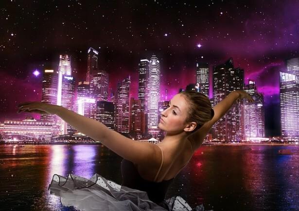 Kobieta tańczy na tle miasta